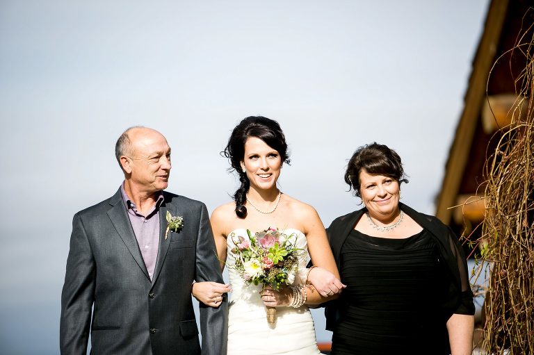 bride walking down the isle with her mom and dad