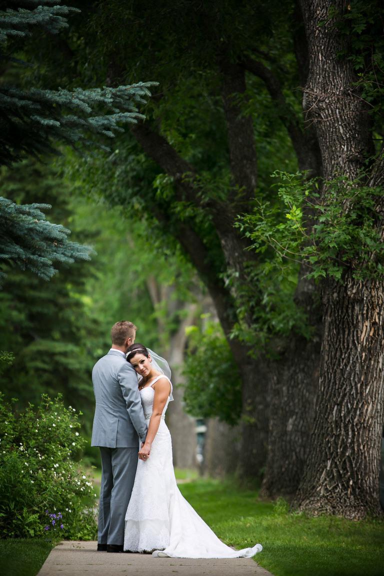 wedding couple hugging under beautiful green trees