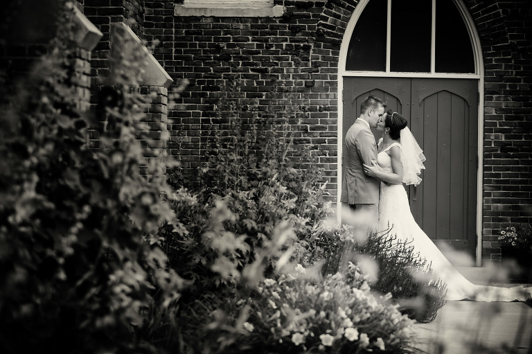black and white photo of a wedding couple kissing in front of the church door
