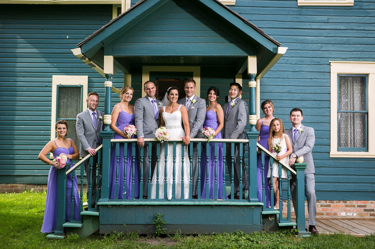 bridal party on a stairs of a blue house