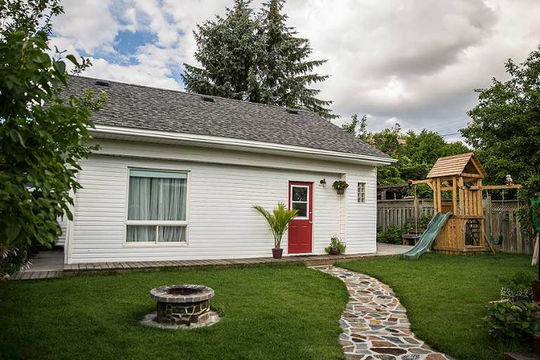 white house on a beautiful yard with red door playground and fireplace